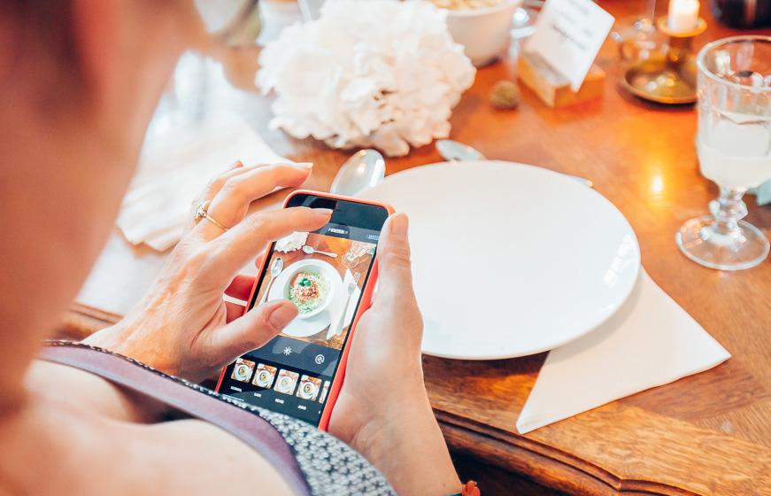 Frau mit Handy fotografiert Essen